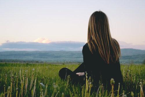 Kobieta siedzi na zielonej trawie