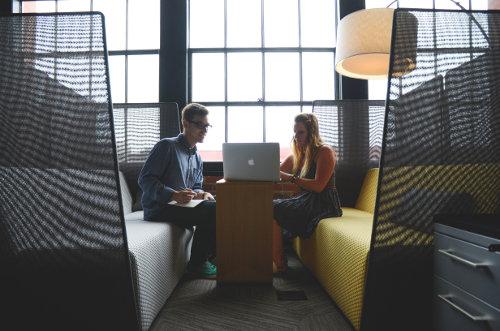 Mężczyzna i kobieta siedzą razem przy laptopie w kawiarni