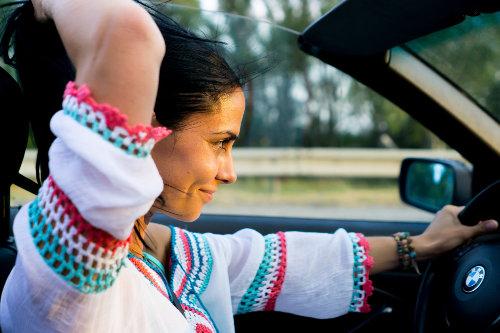 Kobieta z uśmiechem jedzie samochodem w słońcu