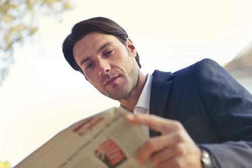 Mężczyzna w garniturze czyta gazetę